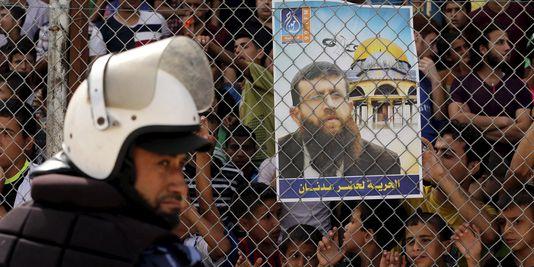 Un policier palestinien devant l'affiche demandant la libération de Khader Adnan, le 7 juin à Gaza. Mohammed Salem / Reuters