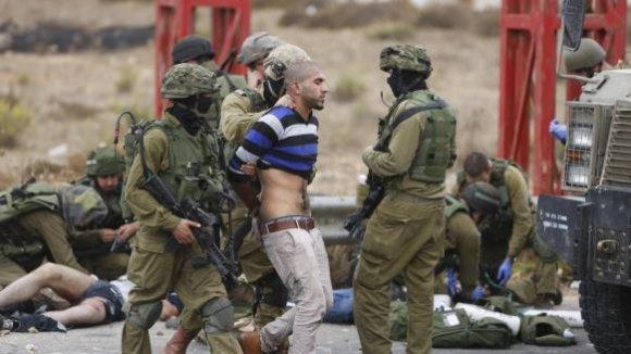 Des soldats israéliens arrêtent un jeune Palestinien après des affrontements à Ramallah (Associated Press)