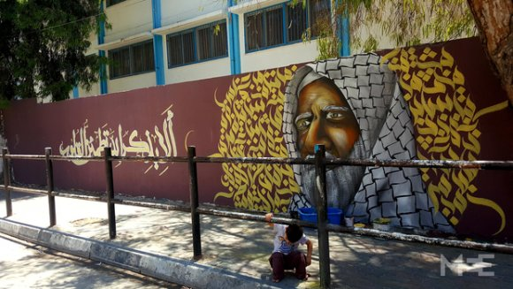Un garçon s'accroupit devant une des peintures de Talaa sur un mur de la ville de Gaza (Baraa Khaled/MEE)