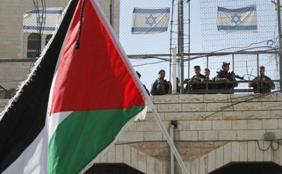Un drapeau national palestinien flotte au passage des soldats israéliens lors d'une manifestation commémorant le jour de l'indépendance de la Palestine à Hébron, en Cisjordanie, le 15 novembre 2016 (AFP)